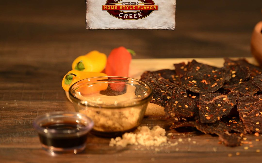 a photo of jerky surrounded by some of its all natural ingredients proving jerky is a healthy snack
